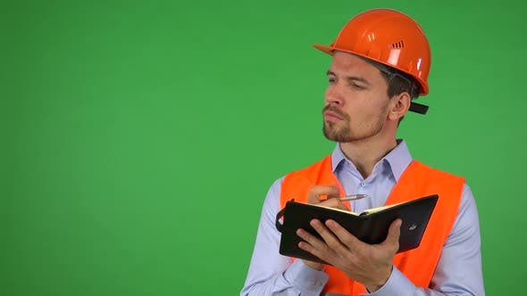 Thumbnail for A Young Handsome Construction Worker Writes Into a Notebook - Green Screen Studio