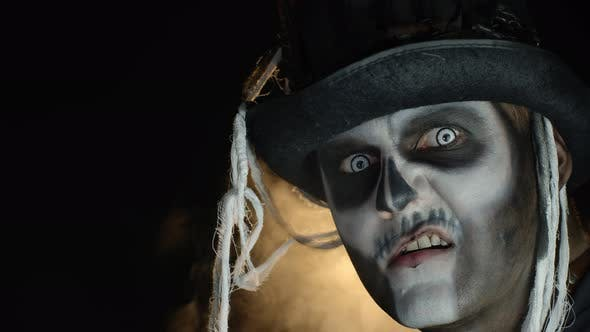 Crazy Man with Horrible Halloween Skeleton Makeup Making Faces, Showing Tongue, Trying To Scare