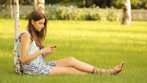 Thumbnail for Girl Sitting in Meadow with Mobile Phone