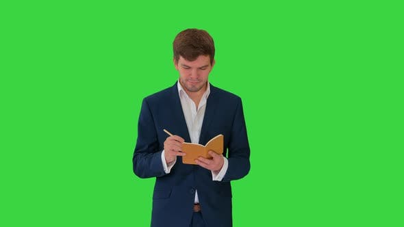 Thumbnail for Young Businessman Thinking and Writing Notes in His Notebook While Walking on a Green Screen, Chroma