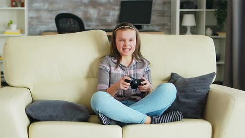 Cheerful Little Girl Playing Video Games Using Wireless Controller
