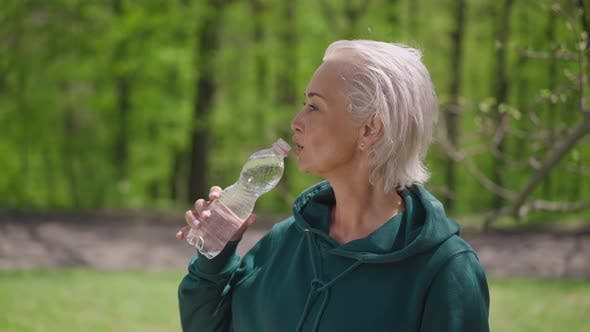 Attractive Senior Sportswoman Drinking Refreshing Water in Slow Motion Looking Away