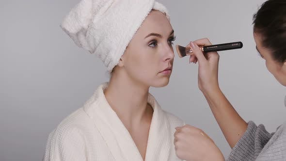 Thumbnail for Make-up Artist Applying Cream on Woman in Bathrobe and Head Towel