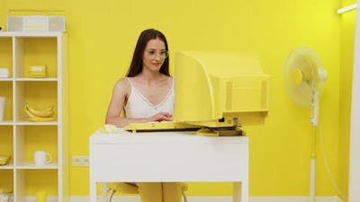 Young Woman Is Typing at Old Yellow PC