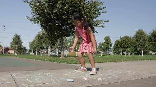 Thumbnail for Young girl playing Hopscotch at park