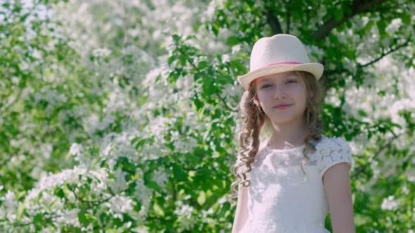 Entzückendes Mädchen stehend in der Nähe von blühenden Bäumen und Lächeln bei der Kamera