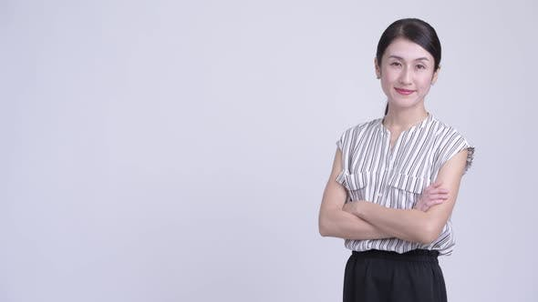 Thumbnail for Profile View of Happy Beautiful Asian Businesswoman Smiling with Arms Crossed