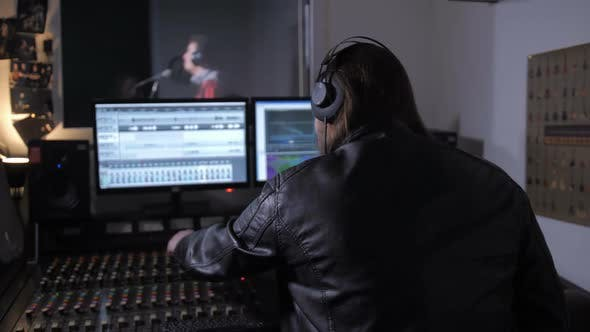 Thumbnail for Music Producer in Headphones Working on Soundboard