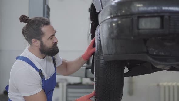 Thumbnail for Handsome Bearded Mechanic Inspecting Suspension or Brakes in Car Wheel of Lifted Automobile