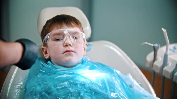 Cover Image for A Little Boy Having His Teeth Done - Putting on Safety Cover and Glasses