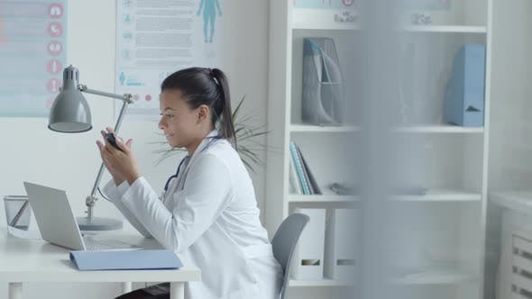 Thumbnail for Female Doctor Using Smartphone at Workplace in Medical Office