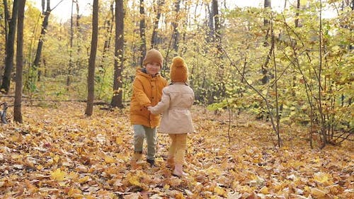 Happy Kids with Little Kids in Autumn Park on Sunny Day