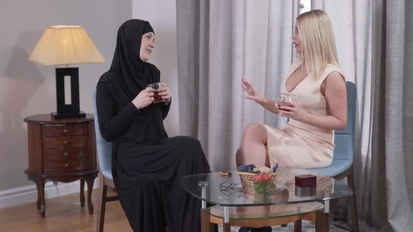 Thumbnail for Side View of Two Different Women Drinking Tea and Talking at Home. People From Caucasian and Muslim