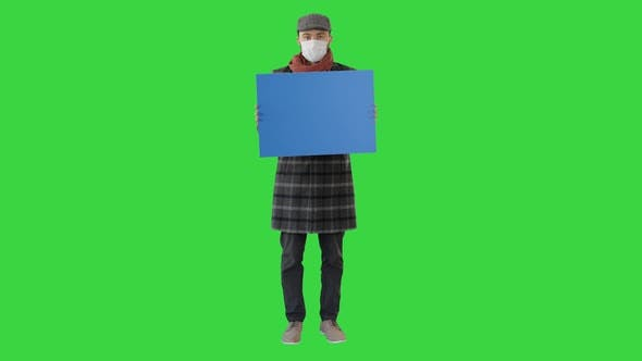 Thumbnail for Man in a Trendy Outfit and Medical Mask Holding Blank Placard on a Green Screen, Chroma Key