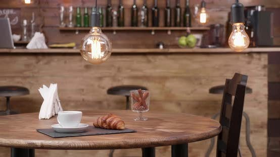 Thumbnail for Slide Shot From Right To Left of a Coffee Shop Table with a Cup of Coffee on It