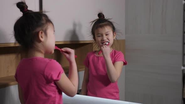 Thumbnail for Cute Asian Girl Brushing Teeth at Bathroom Mirror