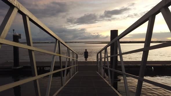 Woman on a dock at sunset
