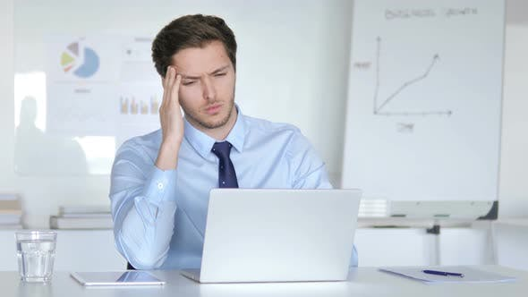Cover Image for Young Businessman with Headache Working in Office