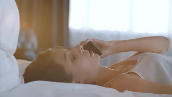 Thumbnail for Pretty Lady Talking on Phone while Resting in Bedroom