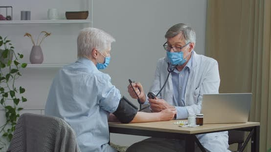 Senior Doctor in Face Mask Measuring High Low Blood Pressure of Elderly Female Patient Woman in