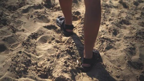 Man In Sandals Walking On Sandy Beach