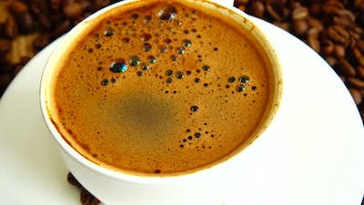 Cup with coffee on the background of coffee beans.