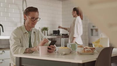 Man Using Smartphone on Breakfast