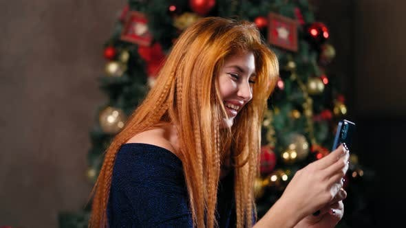 Woman Next To Christmas Tree Uses Smartphone To Communicate Remotely.
