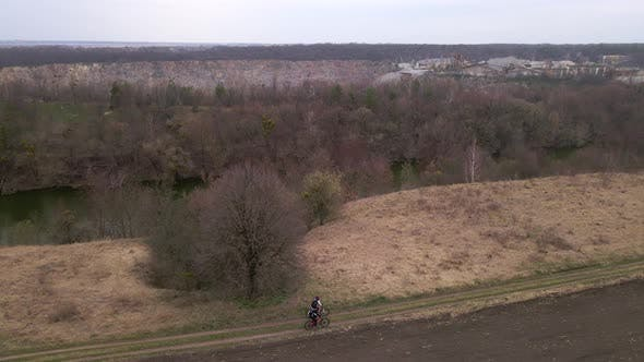 Aerial Shot of Young Sport Men Ride Bicycles on Forest Road at Spring Cloudy Evening