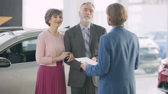Portrait of Confident Wealthy Senior Couple Consulting Car Dealer in Showroom