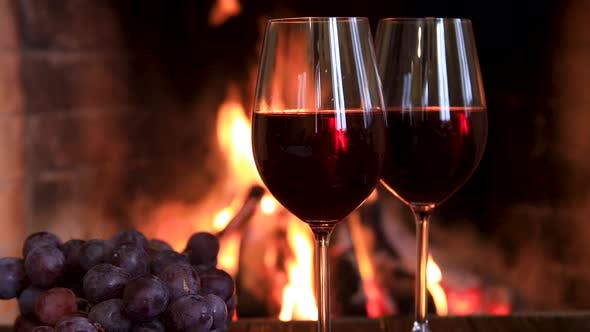 Thumbnail for Two Glasses of Red Wine with Cheese and Grapes Near the Fireplace