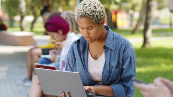 Cheerful Mixed-Race Female Student Using Laptop and Posing for Camera in Park