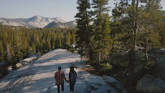 Thumbnail for Aerial Tracking Shot of Young Newlyweds Hiking Together on Amazing White Rock Towards Epic Yosemite