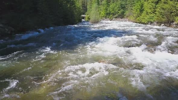 Thumbnail for Aerial Drone Traveling Along Water Rapids With Mountains And Evergreen Forest 2