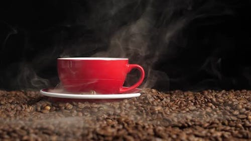Hot Coffee In A Red Coffee Cup And Many Coffee Beans Placed Around