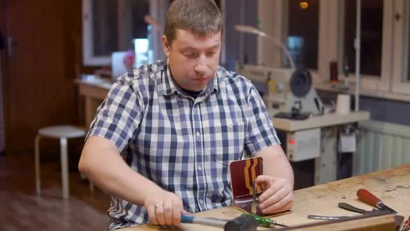 Master of Creating Handmade Leather Wallets Beats a Hammer on the Tool That Makes Holes in the
