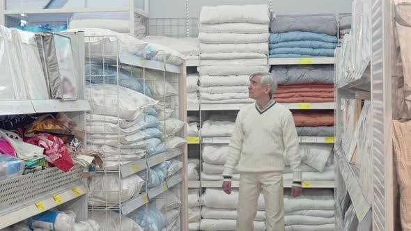 Thumbnail for Elderly Male Customer Choosing Bedding at Home Goods Store