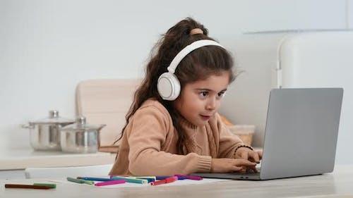 Kleines Mädchen, das Laptop benutzt, Spiele mit Kopfhörern zu Hause