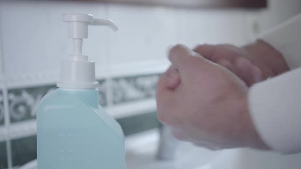 Thumbnail for Close-up of Man Disinfecting Hands with Hand Sanitizer. Male Palms Applying Liquid in Bathroom