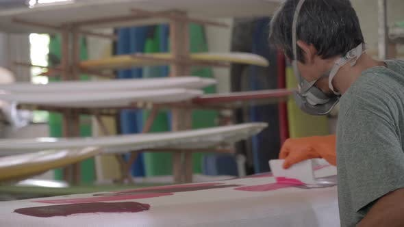 Asian Craftsman Painting Surfboard in Workshop