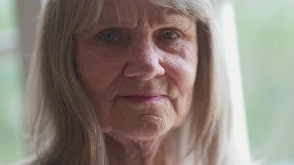 Thumbnail for Close up portrait of friendly looking senior Caucasian woman looking at camera