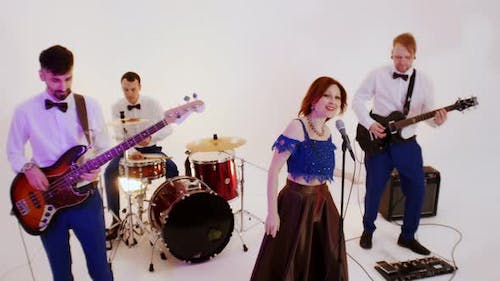 A Musical Band Playing Song in the Bright Studio