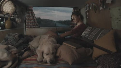 Woman Working on Laptop and Petting Dog in Cozy Camper Van