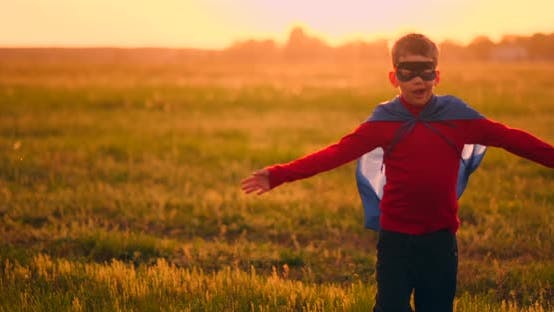 Thumbnail for Boy in Superhero Costume and Mask Running Across the Field at Sunset Dreaming and Fantasizing