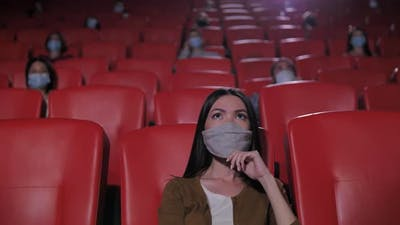 Portrait of Asian Woman in Mask in Movie Theater