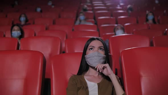 Thumbnail for Portrait of Asian Woman in Mask in Movie Theater