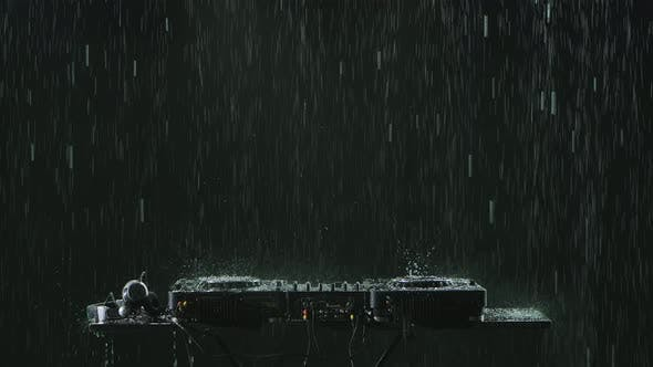 DJ Sound Control Console for Mixing Dance Music and Headphones in the Pouring Rain on the Background