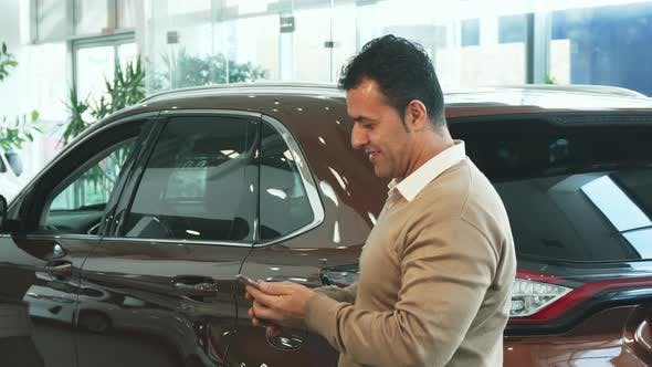 Thumbnail for A Nice Man Makes Selfie on the Background of a New Car