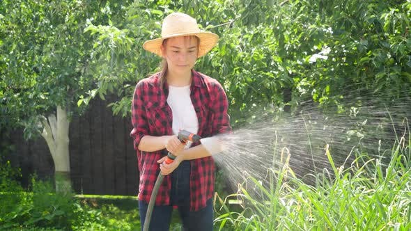 Portrait of Smiling Young Girl Holding Water Hose Watering Growing Vegetables at Backyard Garden