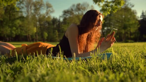 Thumbnail for Happy Girl Typing Sms Lying in Park on Grass. Woman Chatting in Telephone.